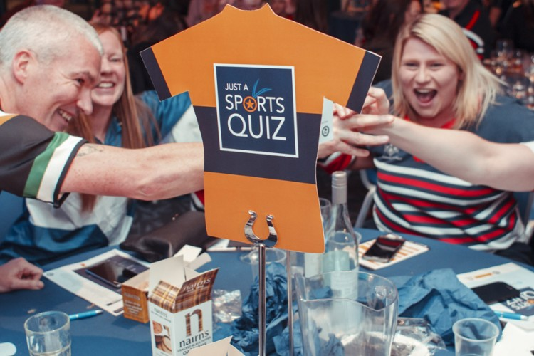 An excited team sitting around a table at Just a Sports Quiz
