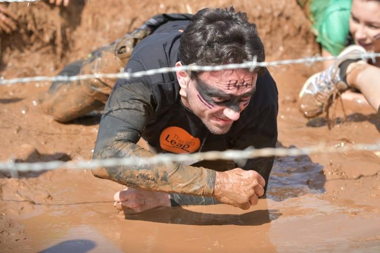 Man crawling through mud under barbed wire
