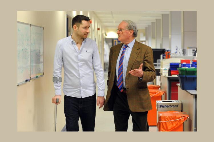 Gordon Aikman and Donald MacDonald walking through a lab talking