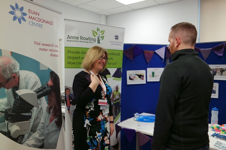 two people talking in front of a stand at the open evening