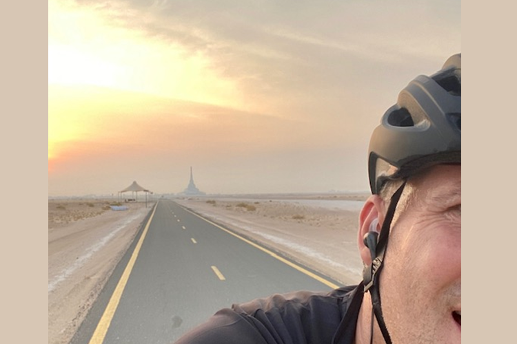 Image of desert road with part of Sandy on a bike in foreground
