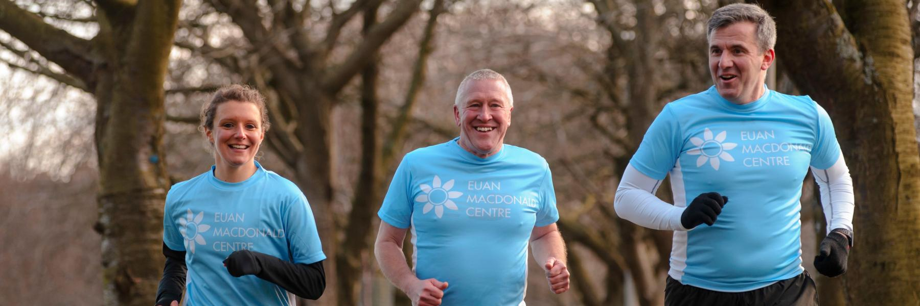 3 people running and smiling in Euan MacDonald Centre T-shirts