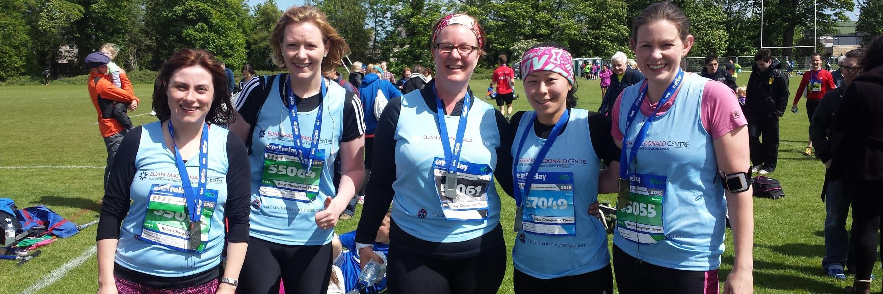 a group of runners wearing medals and Euan MacDonald Centre T-shirts, having just completed the Edinburgh Marathon relay