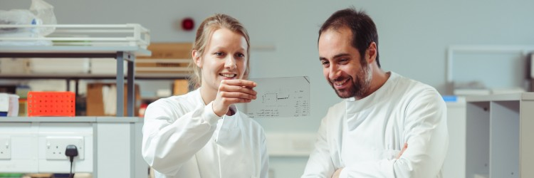 Two researchers in a lab looking at some data