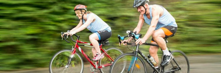 Two people cycling in Euan MacDonald Centre T-shirts