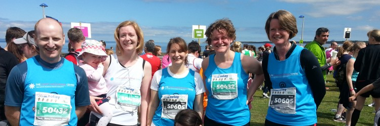 5 people smiling at the camera wearing Euan MacDonald Centre running vests after a race