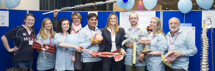 a group of nine Euan MacDonald Centre members at an event, holding props they have used to demonstrate their research