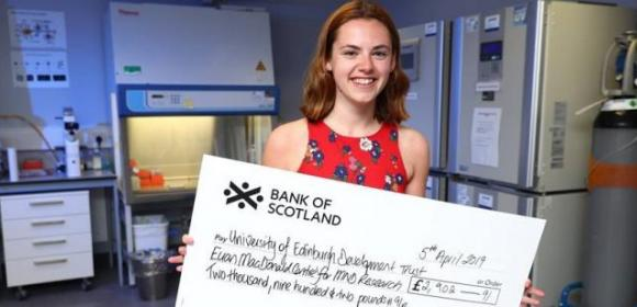 EUSA President Eleri Connick holding a cheque in a lab