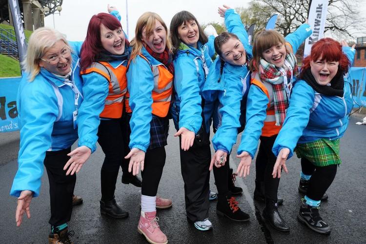 volunteers at the kiltwalk in a line smiling