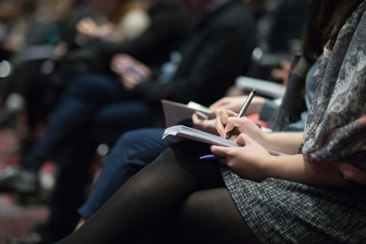 Person writing in a notebook sat in a conference