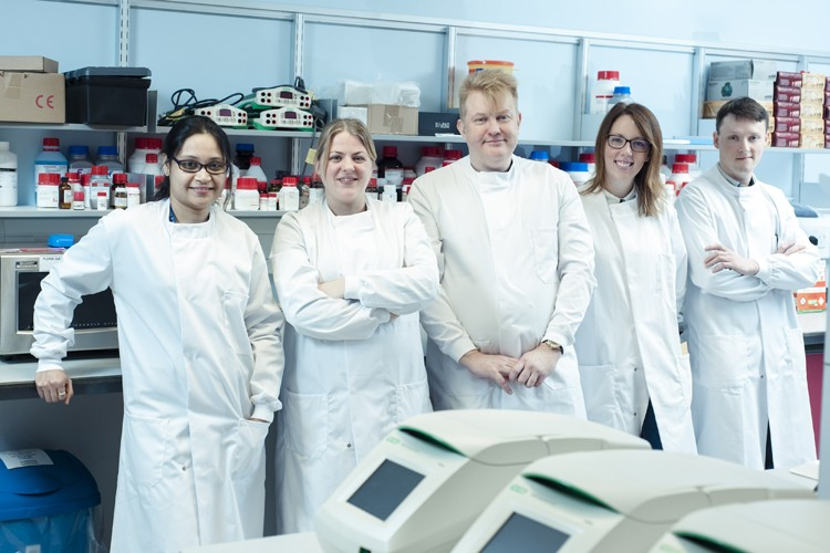 Five researchers wearing lab coats