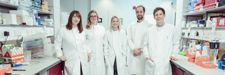 five researchers wearing lab coats standing in a laboratory
